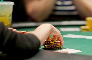poker player reaching for chips